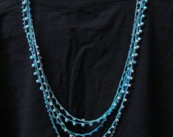 Crocheted necklace with beads aqua blues and sparkle