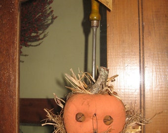 The Man in the Spoon - stuffed fabric jack-o-lantern sitting in a vintage ladle or spoon