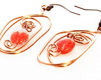 Orange beaded swirl copper wire earrings