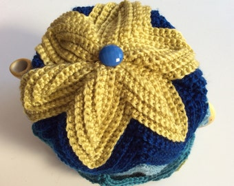 Handmade crocheted tea cosy with chevron/zig zag stripes in shades of blue, green and gold