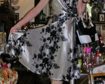 As new floral print black and silver full-sweep classic wrap dress by Events size: 10 ft. split-to-waist skirt and tie/bow sash