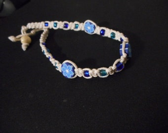 White braided friendship bracelet with blue/black polymer clay flower
