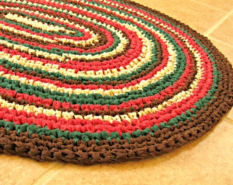 """Crochet oval rag rug, mat, Green, red, brown, ivory.  Bath, cottage, country, country, eco, recycle. 25"""" X 33""""."""
