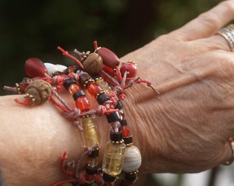 Bracelet made of Three Red & Beige Knotted Hemp Strands Woven Together with Glass and Wood Beads and Gold Tone Metal Findings