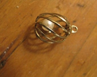 Pearl  in a round gold tone cage with diagnoal bars -  pendant / charm