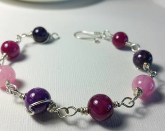 Sterling silver wire wrapped bracelet with pink and purple beads.