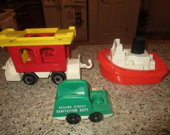 Three Vintage Fisher Price Toys - 1974 Sesame Street Sanitation Dept. Garbage Truck, 1978 Fisher Price Tugboat and 1973 Red Caboose