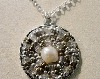 Necklace with Seed Bead Circles In Silver Circle Frame with Fresh Water Pearl. Dangles from Silver Rolo Chain with Seed Beads and Pearls.