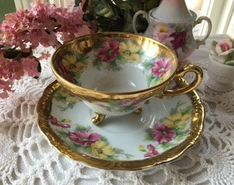 GorgeousThree Legged Japan Teacup and Saucer Set Hand Painted Florrs with Heavy Gold