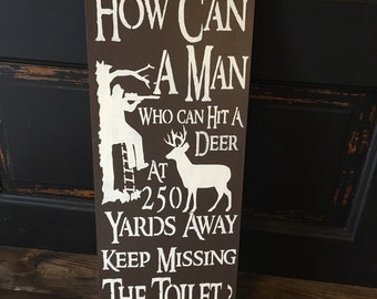How can a man who can hit a deer keep missing the toilet, bathroom sign