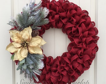 Christmas burlap wreath featuring red burlap, gold poinsettia, and winter spray