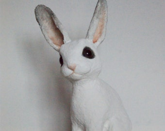 Jenny, a handmade paper clay papier mache sculpture of a young white and grey rabbit