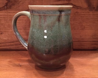 Pottery mug in shades of purple , white , and green