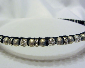 A hand-made headband made of shimmering gold and moonlight-colored rings.