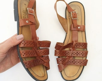 Brown leather asymmetrical strappy sandals. Size 9.