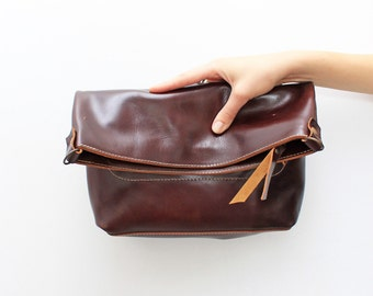 Cognac brown leather clutch with a long strap
