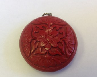 Vintage Chinese cinnabar pendant carved with flowers.