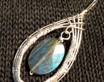 Faceted, Labradorite bead, set into a woven teardrop.