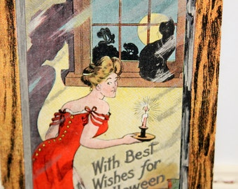 Vintage Halloween Postcard of a lady in red carrying a candlestick up the stairs, black cat and a full moon in window by The Rose Co. 1909