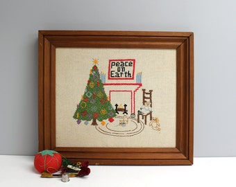 Vintage Peace on Earth cross stitch - 1974 - wooden frame - cozy Christmas scene with tree and fireplace - retro needlework