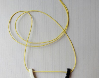 Black and white minimal ceramic pendant on yellow cord