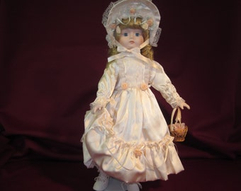"""House of Lloyd """"Tuesday's Child"""" 1989 , 16"""" porcelain doll with stand,blue eyes, peach dress and bonnet,basket,golden locks of hair"""