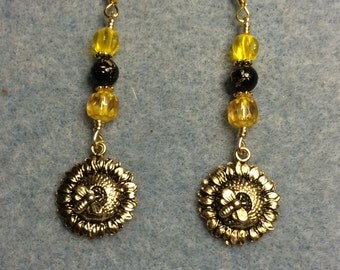 Gold sunflower charm dangle earrings adorned with bright yellow and black Czech glass beads.