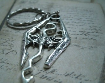 Keychain or Necklace or earring representing a dragon in silver metal