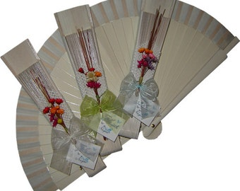 White fan decorated with dried flowers, Ribbon and detail of handmade wedding card