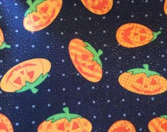 Halloween fabric. Black background with pumpkins and orange glitter