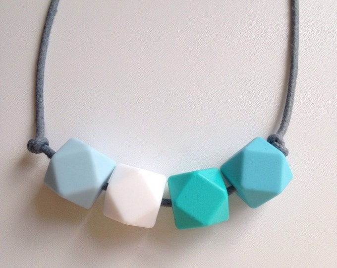 Teething necklace in ice blue, turquoise, white and azure, made from BPA free chewable silicone hexagon beads by Little Gnashers