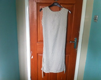 Black and white polka dot sleeveless dress with matching neck tie and belt-fits past the knee.