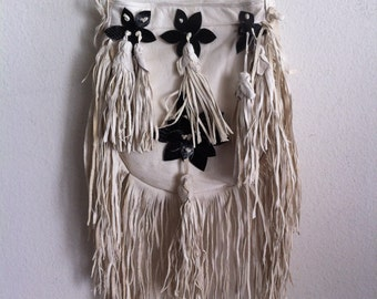 White small bag with a fringe on a long strap, a bag made of genuine leather.