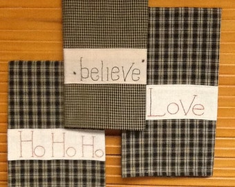 "Tea towels with hand embroidered ""Believe"", ""Love"" or ""Ho Ho Ho"" strips."