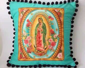 Virgin of guadalupe handmade fabric pom pom cushion, pillow. Turquoise. Robert kaufaman fabric