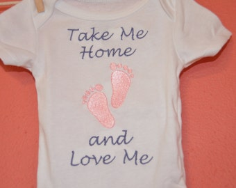 Baby's First Outfit. Design embroidered on a cotton onesie in either pink or blue. Can be personalized.