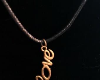 brass tone love charm on a hemp necklace