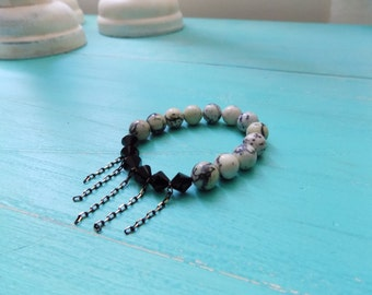 Black and White Serpentine beaded bracelet with black crystal accents and loose dangling chains