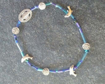 blue glass and silver colored dolphin beaded stretch bracelet