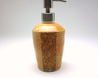 Amber glazed porcelain soap dispenser with with paisley pattern, dots and brushed nickel pump