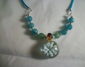 Beautiful Implosion pendant is clear glass surrounding very light blue flower Strung with teal beads on soft teal cord