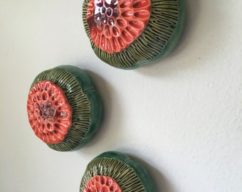 Three Red Orange and Green Bloom Pods Wall Art with Red Glass Centers