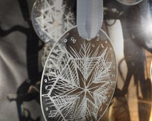 Engraved snowflake hanging decoration. Made from an up-cycled glasses lens. Choose from selection of five.