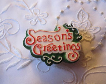 """Vintage Plastic Red, Green and White Christmas Sign """"Season's Greetings"""" Brooch from Hong Kong"""