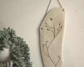 Decorative porcelain wall tile with impression of a dainty plant .  Home decor.