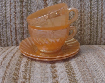 A Pair of Peach Lustre Tea Cups and Saucers