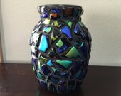 "7"" tall glass vase covered with individual fused, dichroic glass pieces."
