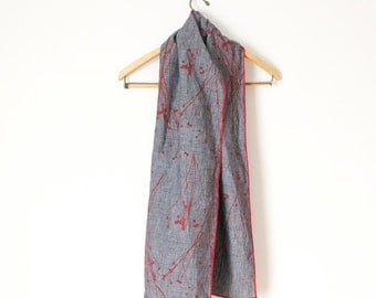 blue gray hand printed linen scarf with red compass flower seed pods edged in red