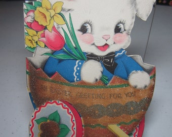 Adorable 1940's die cut glittered Hallmark easter card with cute dressed up bunny sits inside a decorated eggshell with wheels and handle