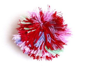 Fiber art brooch using red,purple, pinks, and green threads hand stitched on cream muslin cream felt back abstract design